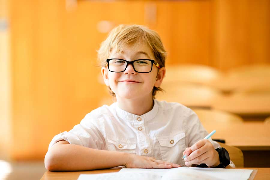a boy smiling while studying at his desk
