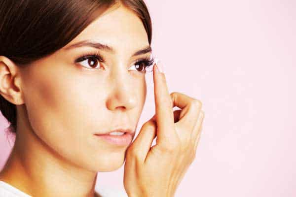 A woman putting on contact lenses on pink background